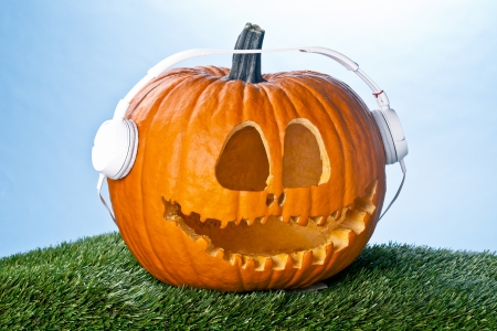 Jack O Lantern pumpkin looking cool wearing a white headset  Stock fotó
