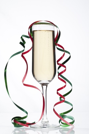 Image of a glass filled with champagne with steamers on it on white background