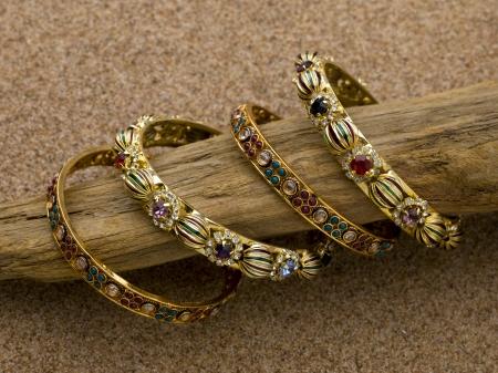 precious stones: Four golden bracelets decorated with precious stones
