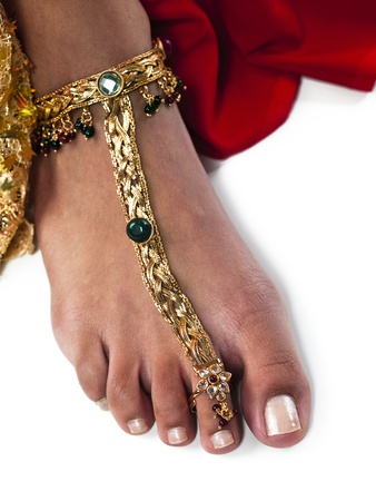 Close-up image of a womans leg wearing gold ankle bracelet over white background. Stock Photo