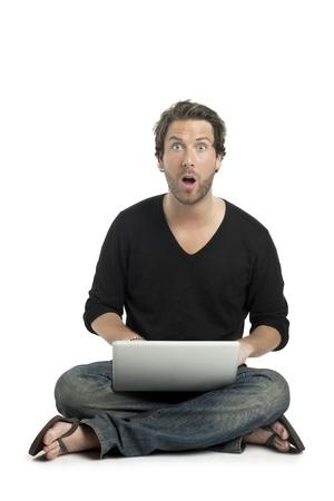 amaze: Close up image of good looking guy shocked while using laptop against white background