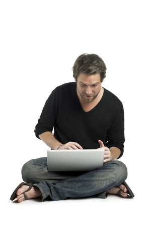 Portrait of good looking guy using laptop while sitting on the floor Stock Photo - 16225574