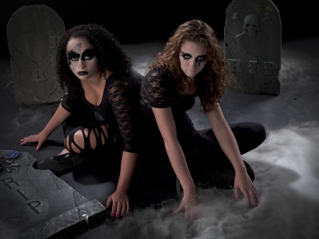 Teens in gothic garb sitting in a cemetary photo