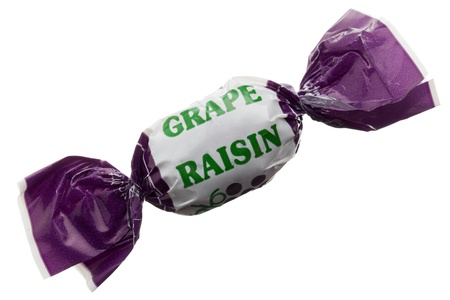 Macro image of a grape raisin candy against the white background Imagens