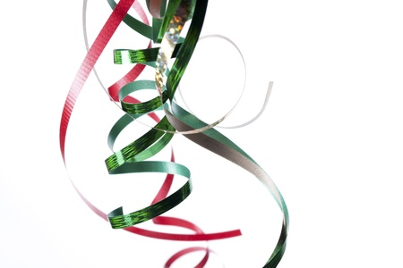 public celebratory event: Green and red shiny streamers against white background.
