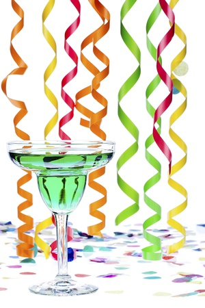 Close-up shot of green alcoholic drink in martini glass with colorful streamers and confetti in background. Stock Photo - 16226247