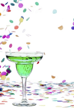 Close-up image of a green drink in martini glass while confetti falling in background. Stock Photo - 16225821