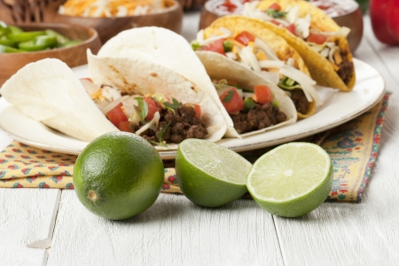 tacos: Closed up shot of a plate of ground beef tacos and lime fruits Stock Photo
