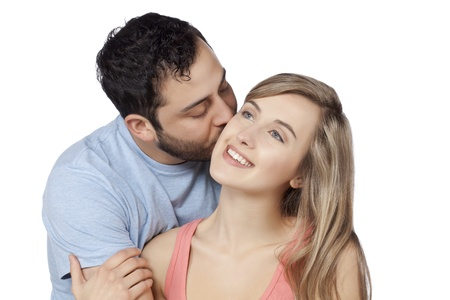 Portrait of guy kissing his girlfriend against white background photo
