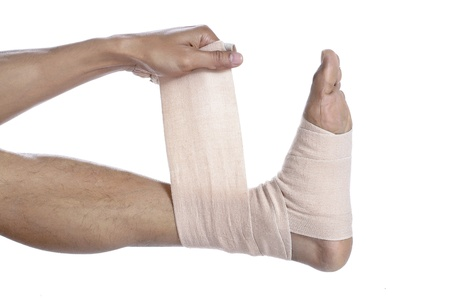 tensor: Close up image of guy placing a tensor bandage on his feet against a white background