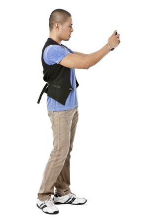 pinoy: Portrait of guy standing while taking picture using phone against white background