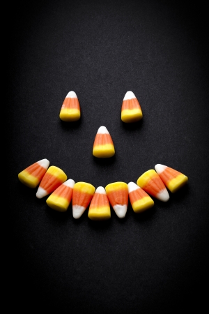 rubbery: Candy corn arranged to create a smiling face against a black background. Stock Photo