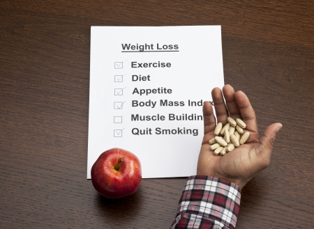 Overhead shot of handful of capsules with an apple and weight loss schedule paper on wooden table