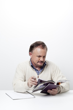 Handsome businessman reading magazine while at work against white background, Model  Dan Sanderson Stock Photo - 16993324