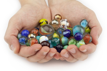 Close-up image of human hand full of colorful round marbles isolated on a white background Archivio Fotografico