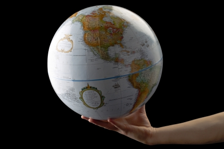 lifting globe: Close-up image of a human hand holding globe in a white surface