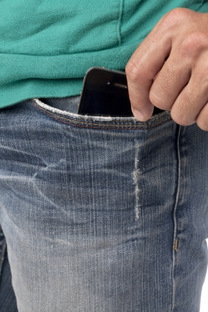 Close-up image of human hand holding phone inside the pocket photo