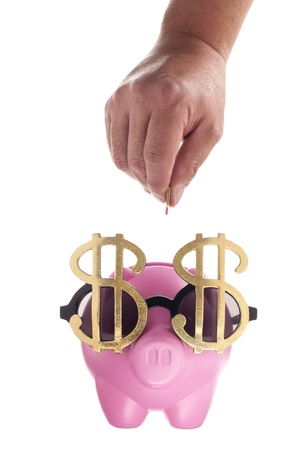 A close-up portrait of a hand with coin on a pink piggy bank over the white background Stock Photo - 16225817