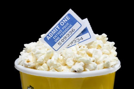 Macro image of full pop corn box with movie tickets above against dark background Stock Photo - 16956446