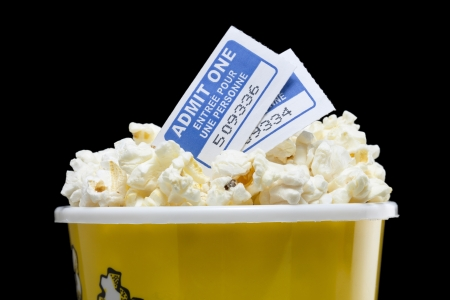 fresh pop corn: Macro image of movie pop corn with tickets above isolated on dark background Stock Photo