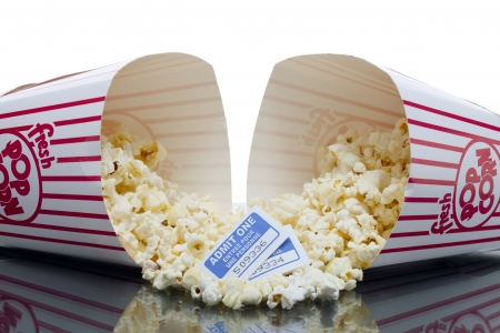 Horizontal image of two buttered popcorn spilled on a red bucket with two movie tickets on the center Stock Photo - 16957638