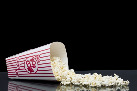 Spilled box of popcorn in a glass table over a black background Stock Photo - 16956122