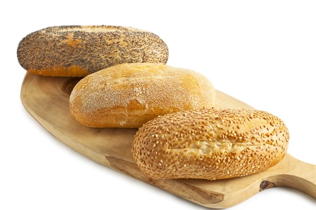 newly baked: Close-up image of three breads on the wooden plank isolated over the white background