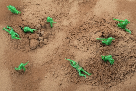plastic soldier: Top view shot of fighting toy soldiers in brown soil