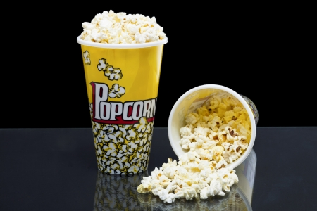 Two cups of popcorn laid in a glass table over a black background