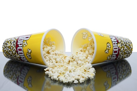 Two cups of spilled popcorn laid in a glass table over white background Stock Photo - 16957587