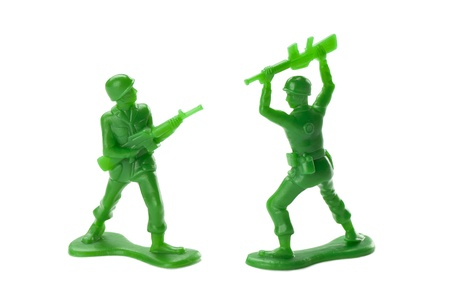 green plastic soldiers: Close-up battle between two military toy soldiers against the white surface Stock Photo