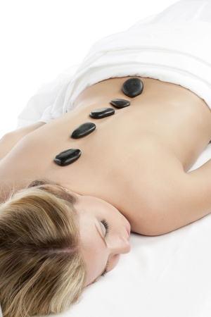 hot stone massage: A beautiful lady lying on the spa with zen stones on her back isolated on a white background