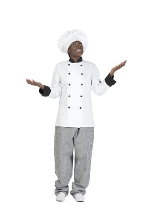 Portrait of a happy female chef looking up with her hand open isolated on a white background Stock Photo - 16986611