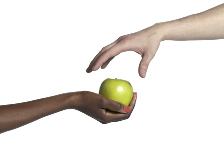 Close-up image of a hand taking an apple from the other hand photo