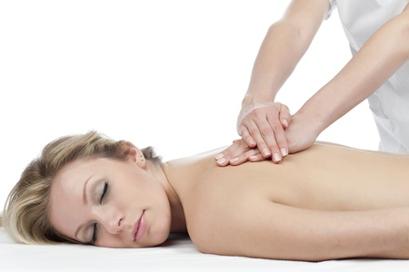 Image of a blonde lady lying on white bed having a back massage photo