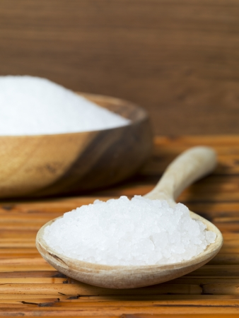 Bowl of salt with wooden spoon in a close-up image photo