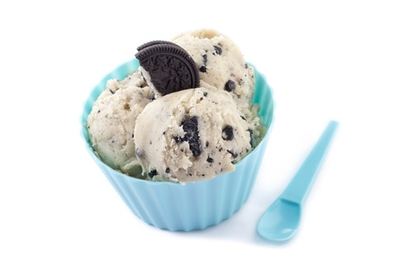 Close up image of cookies and cream in blue clue and blue spoon against white background photo