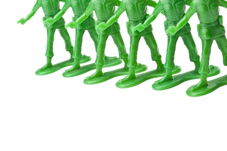 align: Cropped image of green toy soldiers holding a gun align on a white surface