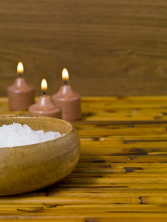 Cropped image of spa salt in bowl with candle on the table photo