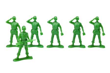 plastic soldier: Green plastic military toys doing a salute to there captain over a white background