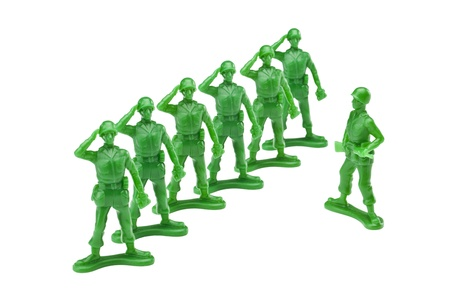 green military miniature: In lined green soldiers miniatures on a salute gesture against white background
