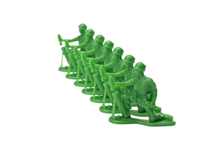 green plastic soldiers: Alignment of green toy soldiers kneeling on the ground of white background