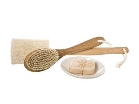 Image of spa tools composed of loofah sponge, brush and soap on a white surface