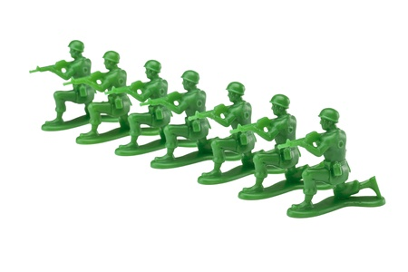 green plastic soldiers: Military toy soldier kneeling on the white surface ready for battle
