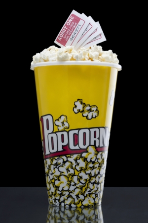 Portrait of pop corn box with several movie tickets above against dark background Stock Photo - 16963797