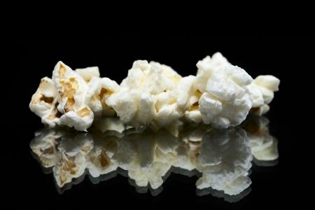 Macro image of pop corn pieces against dark background Stock Photo - 16963497