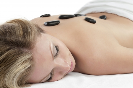 Close-up image of a relaxed woman getting a stone massage therapy over the white background Stock Photo - 16963022