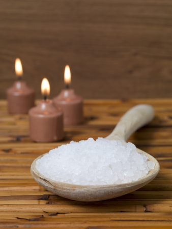 Portrait image of salt on a wooden spoon with candles at the back on a brown wooden background photo