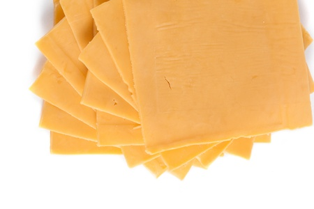 Macro shot in the slices of cheddar cheese arranged on the white background