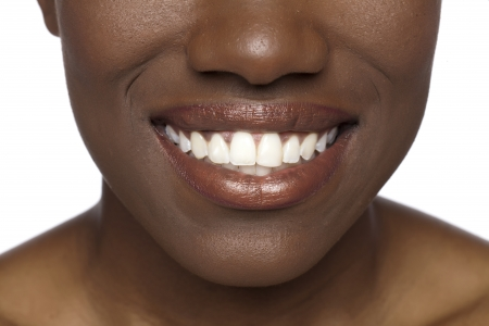 Cropped image of black woman face with toothy smile against white background